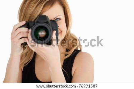 Cute blond-haired woman taking a photo with a camera on a white background