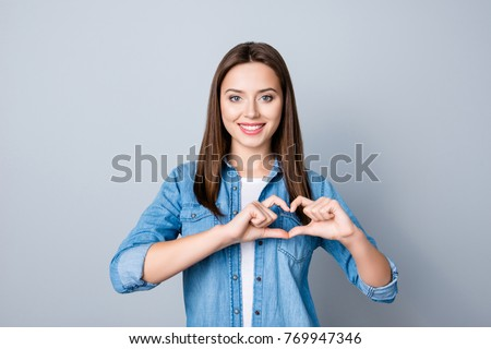Portrait of young, brunette, pretty girl in jeans shirt showing with her finger  heart figure, sending love to her lover, standing over grey background