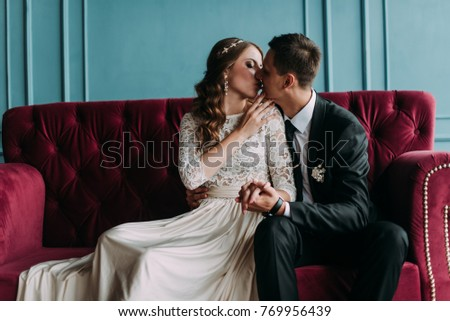 cute wedding couple in the interior of a classic studio decorated. hey kiss and hug each other #769956439