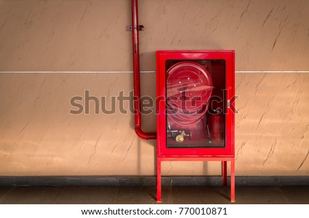 Fire extinguisher and fire hose reel in hotel corridor #770010871