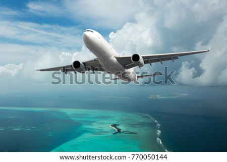A passenger plane in the cloudy sky. Aircraft flies over the sea and the tropical island. Royalty-Free Stock Photo #770050144