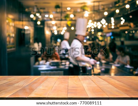 Wood table top with blur chef cooking in bar restaurant background.For create product display or design key visual layout #770089111