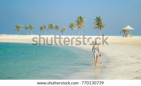 Blond hair in hat girl walking without shoes by seaside e with a palm trees on the background #770130739