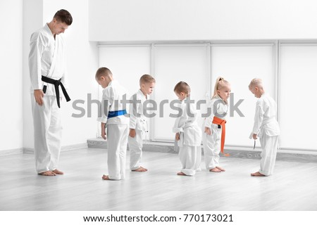 Little children and instructor performing ritual bow prior to practicing karate in dojo #770173021