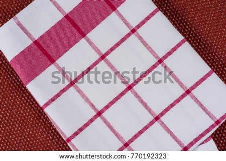 Background for product. Checked tablecloth in a red and white cage on textured surface, view from above. #770192323