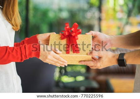 closeup picture of man and woman's hands with gift box	 #770225596