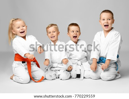 Little children in karategi on light background Royalty-Free Stock Photo #770229559