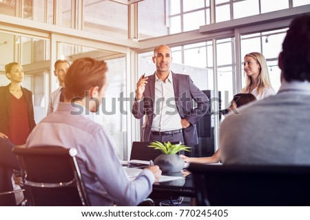 Senior man talking to employees in office meeting. Marketing team discussing new ideas with manager during a conference. Senior leadership training future businessmen and businesswomen. Royalty-Free Stock Photo #770245405