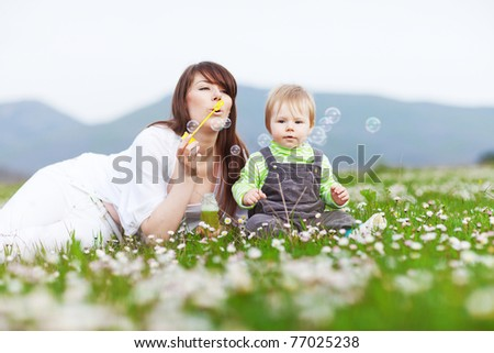 happy child and woman outdoor playing with soap bubble on meadow #77025238