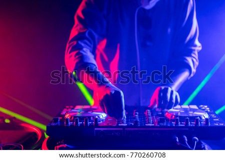 DJ playing music on light background Royalty-Free Stock Photo #770260708
