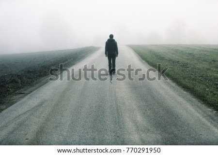Man standing alone on rural foggy and misty asphalt road. Royalty-Free Stock Photo #770291950
