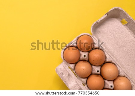 Overhead view of brown chicken eggs in an open egg carton isolated on yellow. Fresh chicken eggs background.  Top view with copy space. Natural healthy food and organic farming concept. Eggs in box #770354650