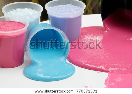 Bottles of Homemade Plaything Called Slime, Colorful of Science Toy in Container Spill on Table, Selective focus on Slime. #770371591