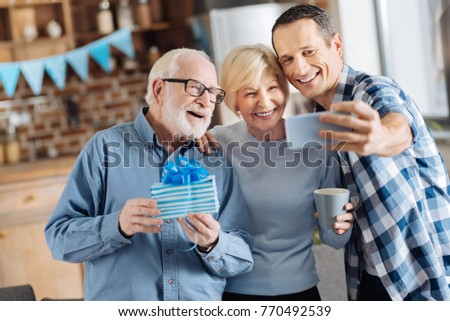 Seizing the moment. Cheerful young man taking selfies with his elderly parents during the celebration of the fathers birthday while the man holding a gift box #770492539