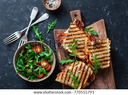 Grilled bacon, mozzarella sandwiches on wooden cutting boards and arugula, cherry tomato salad on dark background, top view.Delicious breakfast or snack, flat lay     #770555791