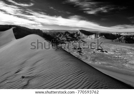 Black and white image, great dune and the amphitheater in the background under a beautiful sky with feathery clouds, Valle de la Luna, Atacama desert, Chile #770593762