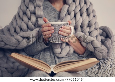 Cozy Woman covered with warm soft merino wool blanket reading a book. Relax, comfort lifestyle. Royalty-Free Stock Photo #770610454