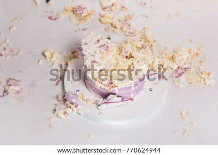 Smashed cake on white table for first birthday. Messy pieces Royalty-Free Stock Photo #770624944