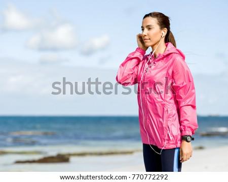 Sporty woman with earphones on the sea coast #770772292