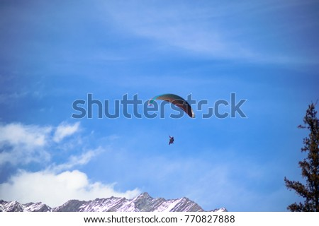Paragliding with blue sky in the background at Manali, Himachal Pradesh, India.. #770827888