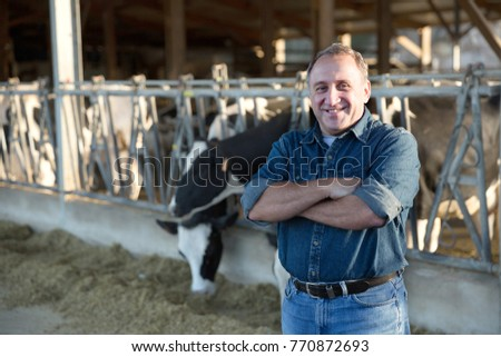 Portrait of successful mature male farmer in cowshed #770872693
