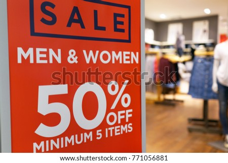 Sale up to 50% off text on a sign board inside a popular clothing store  #771056881