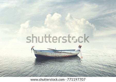 man relaxing on old boat floating in the calm water #771197707