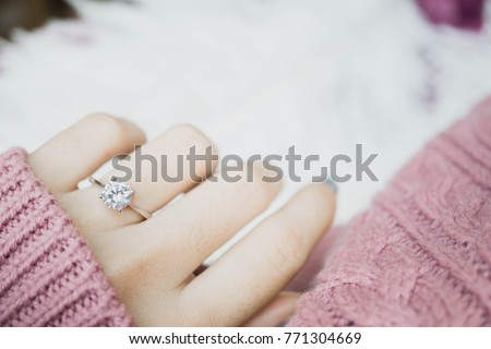 Close up of an elegant engagement diamond ring on woman finger with dark pink sweater winter clothe. love and wedding concept. #771304669