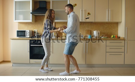 Attractive young funny couple have fun dancing while cooking in the kitchen at home #771308455