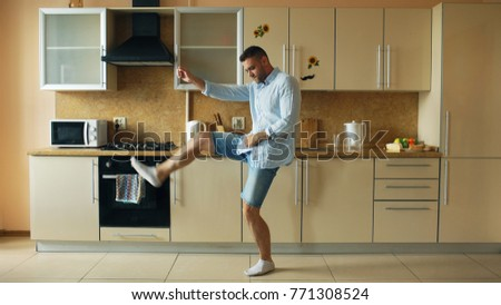Handsome young funny man dancing in kitchen at home in the morning and have fun on holidays #771308524