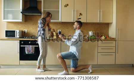 Young man making proposal to his girlfriend in the kitchen at home #771308587