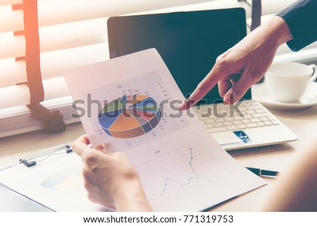 Business adviser analyzing and discussing financial figures denoting the progress in the work of the company.  Business Concept. #771319753