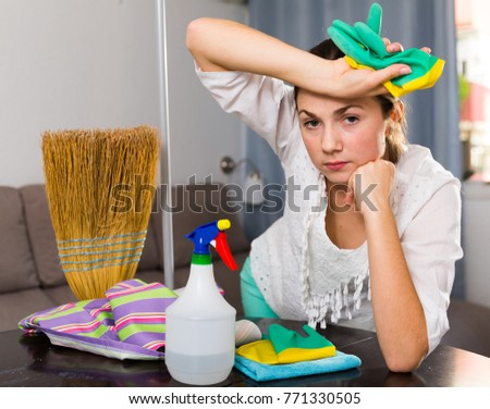 Forworn sad girl cleaning kitchen in the house #771330505