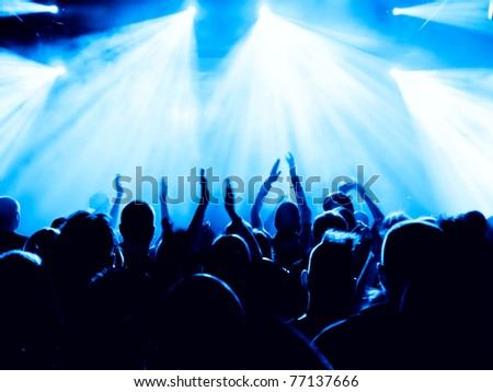 silhouettes of concert crowd in front of bright stage lights #77137666