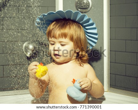 Cute happy smiling funny undressed boy child in blue hat with blonde curly wet hair taking shower in bath with water indoor playing with toy duckling, horizontal picture