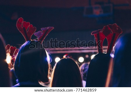 rear view of audience wearing christmas deer horns at a christmas concert. silhouettes of concert crowd in front of bright stage lights.