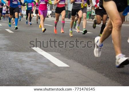 Crowd of people are running a marathon around the city. The race of amateurs and professionals. Out of focus #771476545