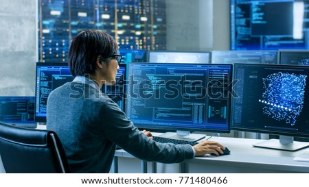 In the System Control Room Technical Operator Works at His Workstation with Multiple Displays Showing Graphics. IT Technician Works on Artificial Intelligence, Big Data Mining, Neural Network Project. #771480466