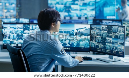 In the Security Control Room Officer Monitors Multiple Screens for Suspicious Activities. He's Surrounded by Monitors and Guards Facility of National Importance. #771480622