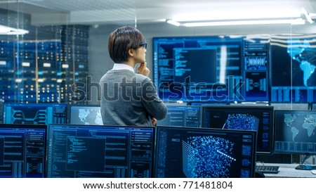 In the System Control Room Technical Operator Stands and Monitors Various Activities Showing on Multiple Displays with Graphics. Administrator Monitors Work of  Artificial Intelligence. #771481804