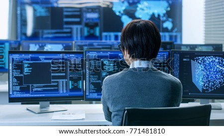 In the System Control Room Technical Operator Works at His Workstation with Multiple Displays Showing Graphics. IT Technician Works on Artificial Intelligence, Big Data Mining, Neural Network Project. #771481810