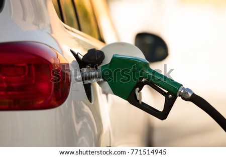 white car at gas station being filled with fuel #771514945