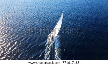 Aerial drone birds eye view photo of beautiful sailboat with white sails cruising in the deep blue Aegean sea, Greece #771617185
