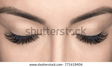 Eyelash extension procedure. Beautiful Woman with long lashes in a beauty salon.  Royalty-Free Stock Photo #771618406