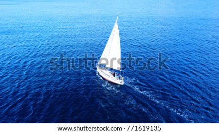 Aerial drone top view photo of sail boat sailing in mediterranean Aegean island of Santorini, Cyclades, Greece #771619135