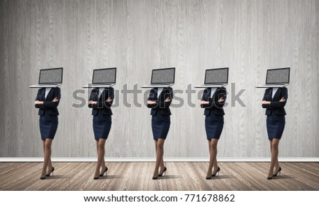 Business women in suits with laptops instead of their heads keeping arms crossed while standing in a row in empty room with gray wall on background. #771678862