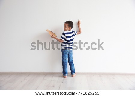 Little African-American boy painting on wall indoors #771825265