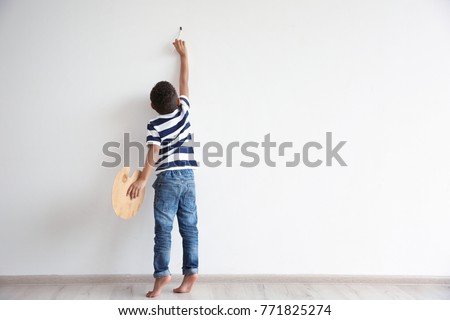 Little African-American boy painting on wall indoors #771825274
