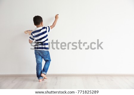 Little African-American boy painting on wall indoors #771825289