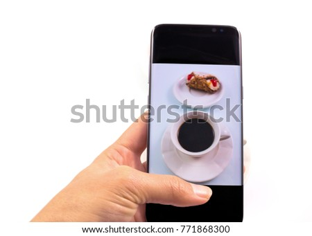 hands taking picture coffee and sweet cookie with a smart phone in white background.